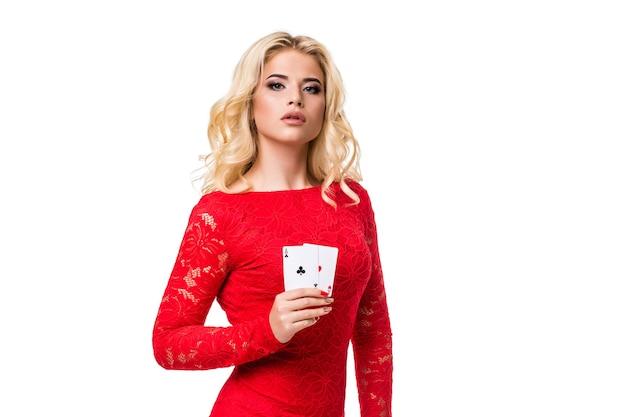 Mulher jovem caucasiana com cabelo loiro longo claro em traje de noite, segurando cartas de jogar. isolado. pôquer