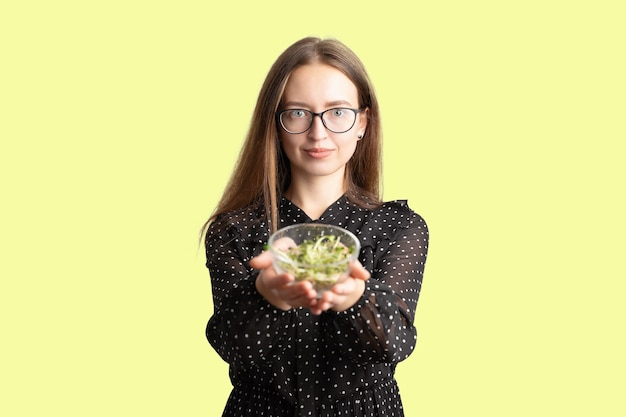 Mulher jovem caucasiana com salada isolada na parede branca. superalimento de microgreens.