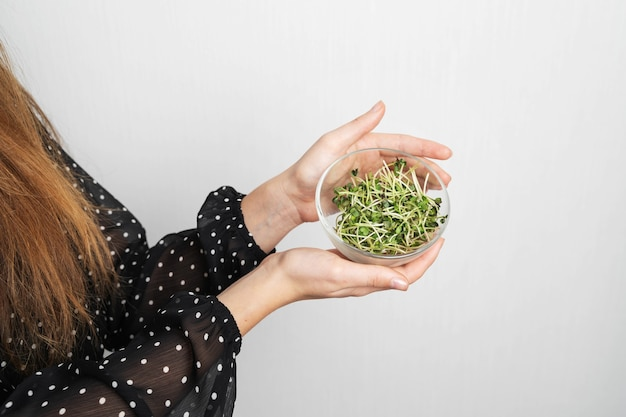 Mulher jovem caucasiana com salada isolada na parede branca. superalimento de microgreens. Foto Premium