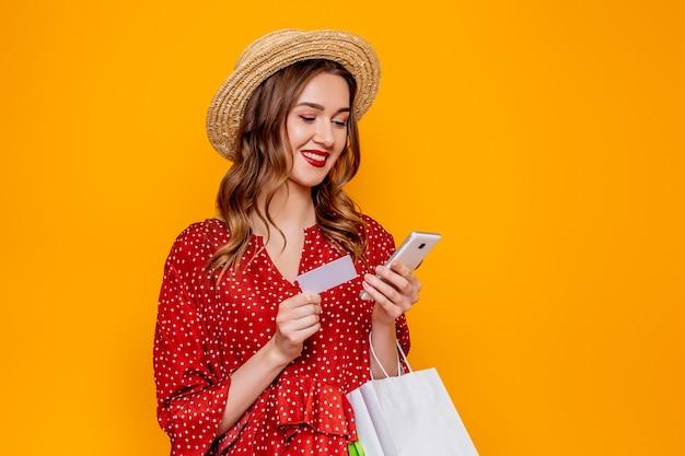 Mulher jovem caucasiana com vestido vermelho de verão com chapéu de palha sorrindo e segurando um cartão de crédito, telefone celular e pacote de compras e olhando para a tela do telefone isolada na parede laranja do estúdio