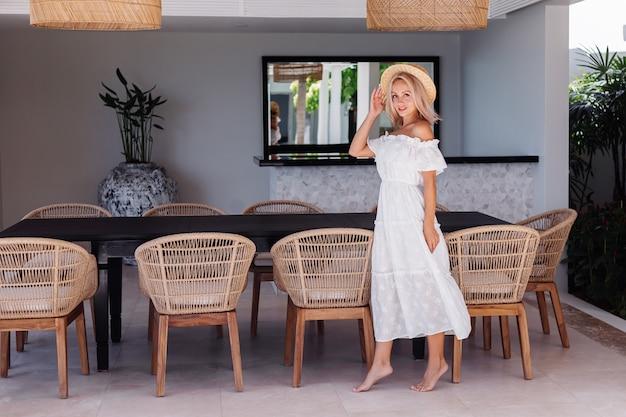Mulher jovem caucasiana de cabelos loiros bonitos na cozinha ao ar livre em villa. mulher com maquiagem leve, vestido de verão branco e chapéu de palha nas férias