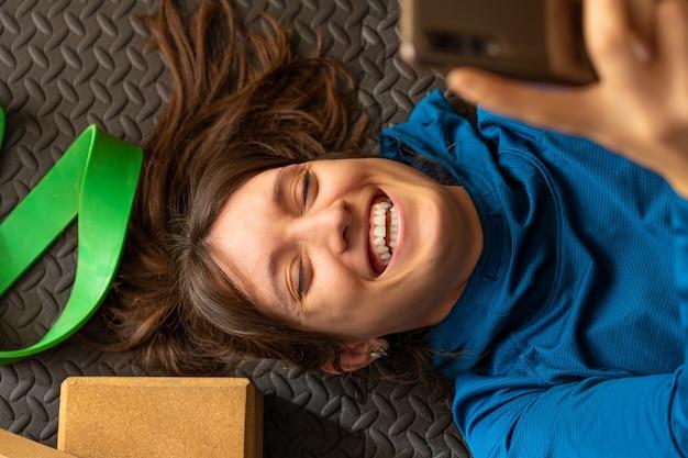 Mulher jovem caucasiana em roupas esportivas deitada no chão de uma academia de costas usando seu telefone celular, garota ri muito enquanto usa suas redes sociais