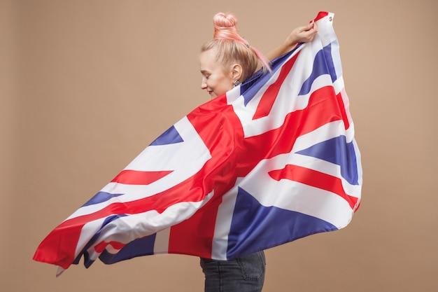 Mulher jovem caucasiana hippie com bandeira da grã-bretanha