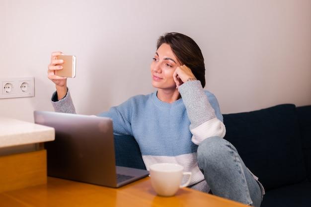 Mulher jovem caucasiana no quarto no sofá olhando para a câmera do celular