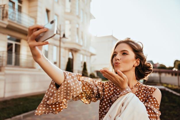 Mulher jovem caucasiana refinada usando telefone para selfie em dia de outono. tiro ao ar livre do glamouroso modelo feminino em roupas marrons, enviando beijo no ar.