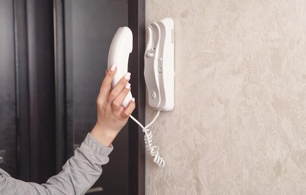 Mulher jovem caucasiana, segurando o receptor de interfone.