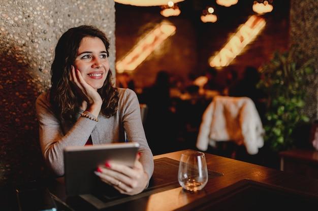 Mulher jovem caucasiana sorridente em um restaurante segurando e usando um tablet
