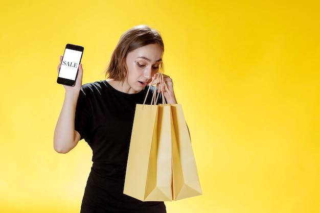 Mulher jovem caucasiana, sorrindo e segurando um telefone celular, e um pacote de compras olhando para a tela do telefone
