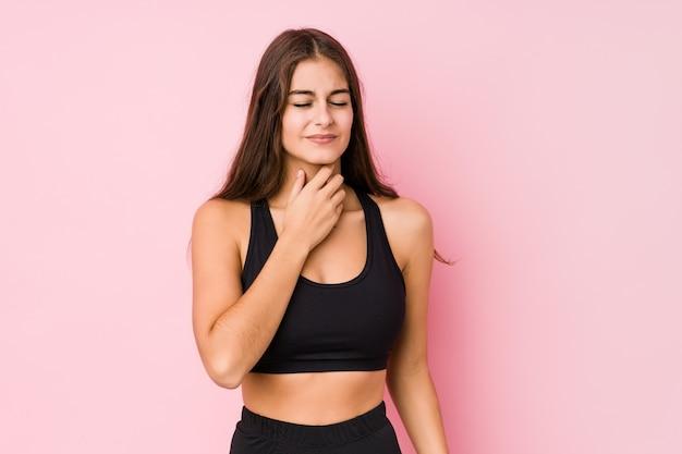 Mulher jovem caucasiano fitness fazendo esporte sofre dor na garganta devido a um vírus