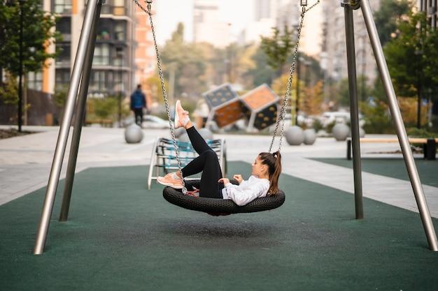 Mulher jovem cavalga em um balanço. menina descansando no playground.
