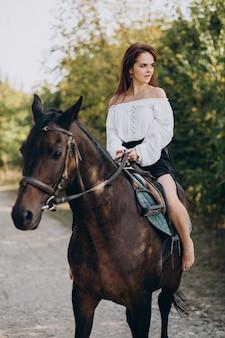 Mulher jovem cavalgando na floresta