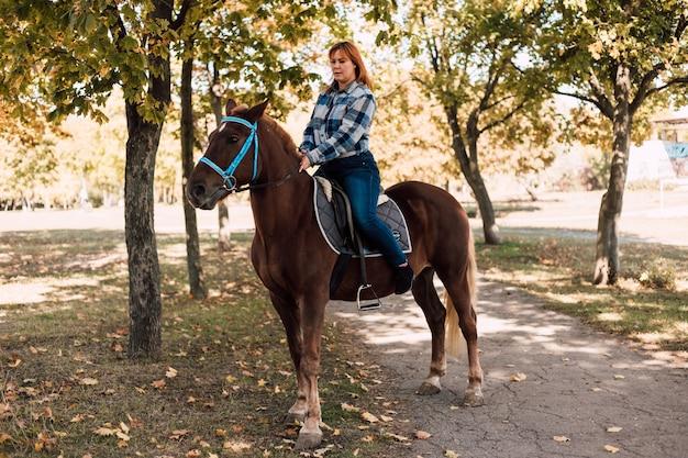 Mulher jovem, cavalgando um cavalo marrom, caminhando no parque de outono em um dia ensolarado