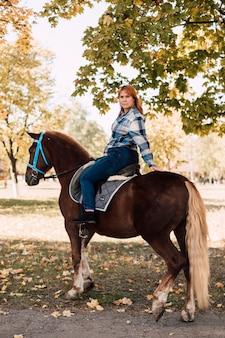 Mulher jovem cavalgando um cavalo marrom, posando de meia-volta, caminhando no parque de outono em um dia ensolarado