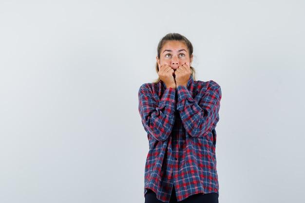 Mulher jovem cerrando os punhos, colocando os punhos nas bochechas com uma camisa xadrez e parecendo assustada