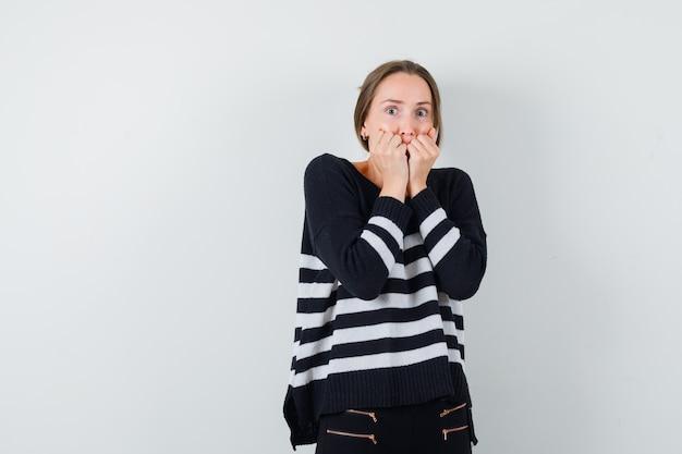 Mulher jovem cerrando os punhos e segurando a boca com as mãos em malha listrada e calça preta, parecendo assustada