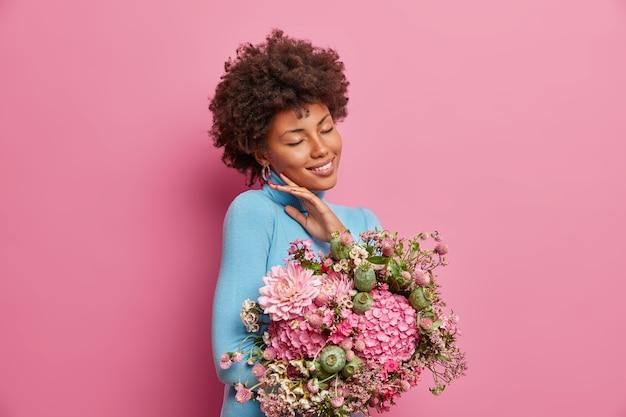 Mulher jovem charmosa com sorriso gentil, toca o rosto, fica de pé, de olhos fechados, recebe buquê de flores dos colegas em homenagem à promoção, modelos