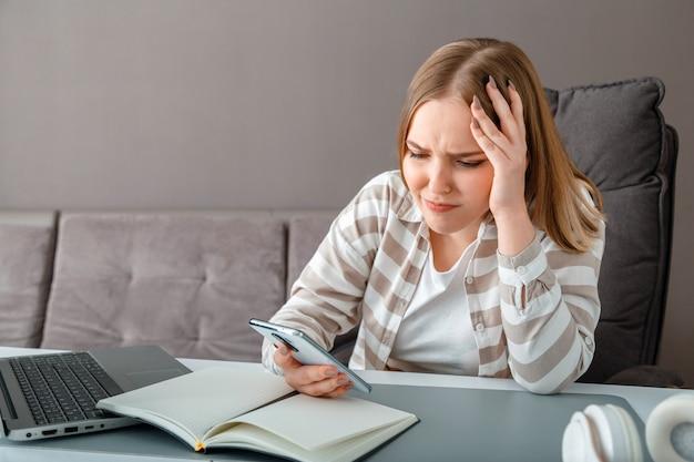 Mulher jovem chateada com o estresse. mulher confusa, segurando a cabeça, recebeu más notícias via smartphone no trabalho. menina adolescente olha para a tela do smartphone durante a depressão de emoções negativas de trabalho ou educação on-line.