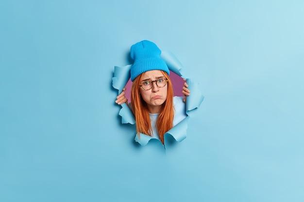 Mulher jovem chateada decepcionada franze os lábios com expressão ofensiva parece tristemente tem cabelo ruivo comprido usa chapéu e óculos transparentes enfia a cabeça para fora do buraco rasgado da parede de papel azul.