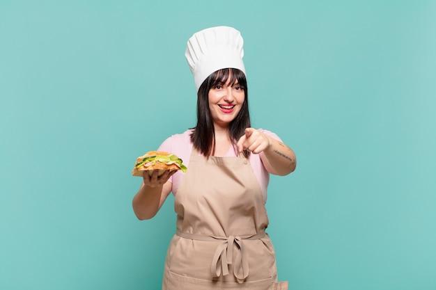 Mulher jovem chef apontando para a câmera com um sorriso satisfeito, confiante e amigável, escolhendo você