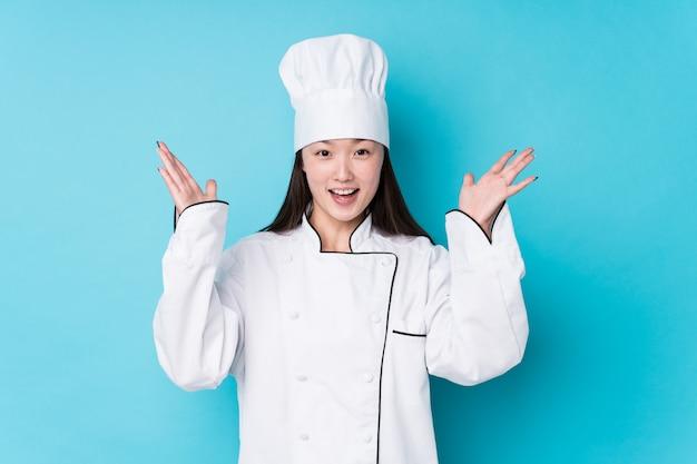 Mulher jovem chef chinês isolado recebendo uma surpresa agradável, animado e levantando as mãos.