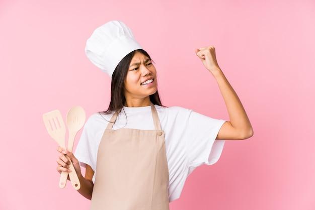 Mulher jovem chef chinesa isolada levantando o punho após uma vitória, o conceito de vencedor.