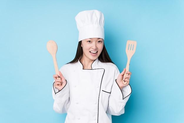 Mulher jovem chef japonesa com ferramentas de cozinha