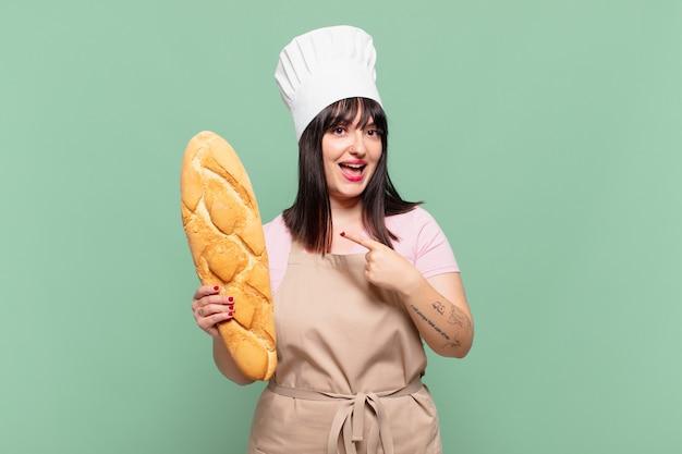 Mulher jovem chef parecendo animada e surpresa apontando para o lado e para cima para copiar o espaço