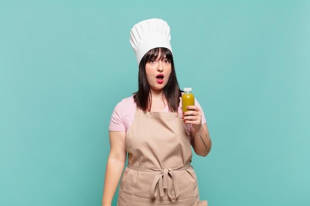Mulher jovem chef parecendo muito chocada ou surpresa, olhando com a boca aberta dizendo uau