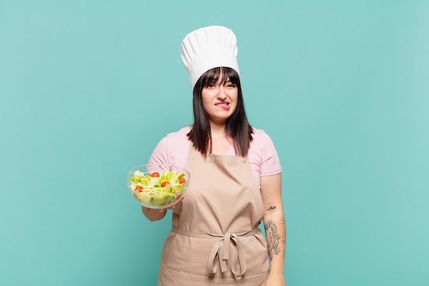 Mulher jovem chef parecendo perplexa e confusa, mordendo o lábio com um gesto nervoso, sem saber a resposta para o problema