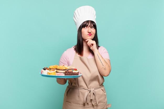 Mulher jovem chef pensando, se sentindo duvidosa e confusa, com opções diferentes, imaginando qual decisão tomar