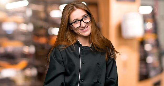 Mulher jovem chef ruiva com óculos e feliz na padaria