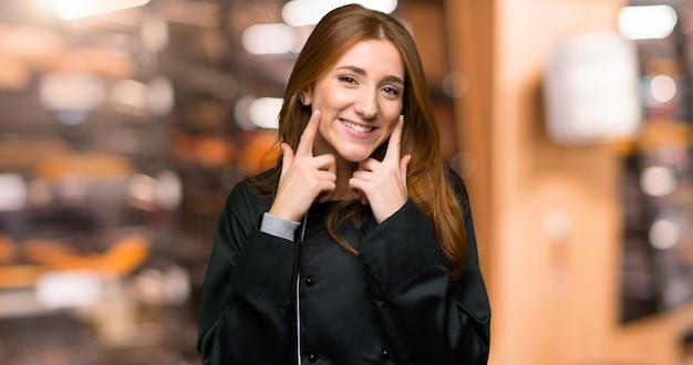 Mulher jovem chef ruiva sorrindo com uma expressão feliz e agradável na padaria