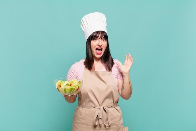 Mulher jovem chef se sentindo feliz, animada, surpresa ou chocada, sorrindo e espantada com algo inacreditável