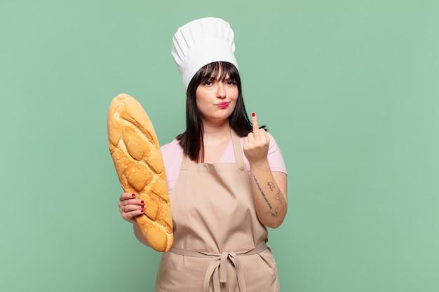 Mulher jovem chef se sentindo irritada, irritada, rebelde e agressiva, sacudindo o dedo do meio e revidando
