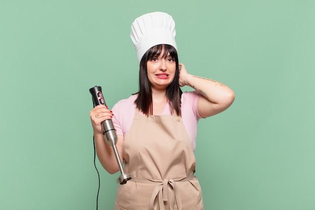 Mulher jovem chef sentindo-se estressada, preocupada, ansiosa ou com medo, com as mãos na cabeça e entrando em pânico com o erro