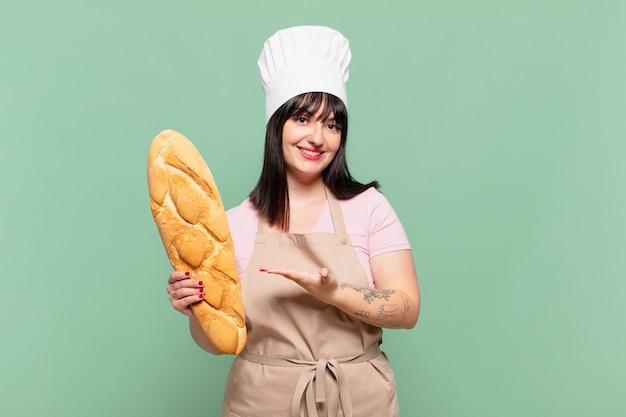 Mulher jovem chef sorrindo alegremente, sentindo-se feliz e mostrando um conceito no espaço da cópia com a palma da mão