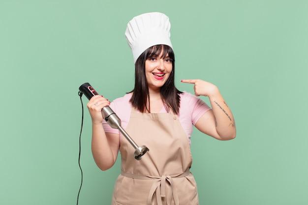 Mulher jovem chef sorrindo com confiança apontando para o próprio sorriso largo, atitude positiva, relaxada e satisfeita
