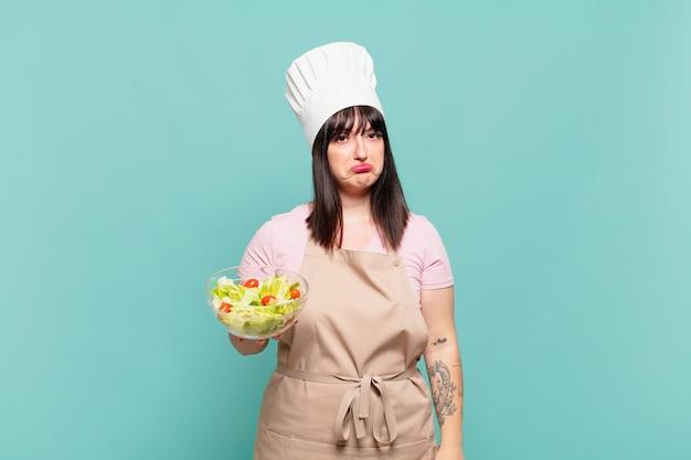 Mulher jovem chef triste e chorona com uma expressão infeliz, chorando com uma atitude negativa e frustrada