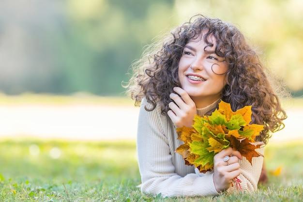Mulher jovem cheia de emoções da temporada de outono. menina com aparelho dentário e cabelo encaracolado.