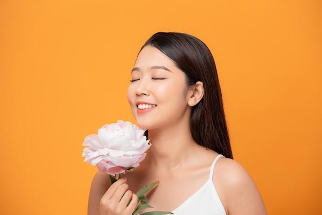 Mulher jovem cheirando a flor de peônia rosa fechou os olhos no fundo amarelo