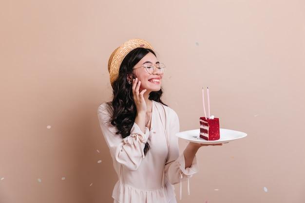 Mulher jovem chinesa sorridente comemorando aniversário. mulher asiática de jocund segurando o prato com bolo.