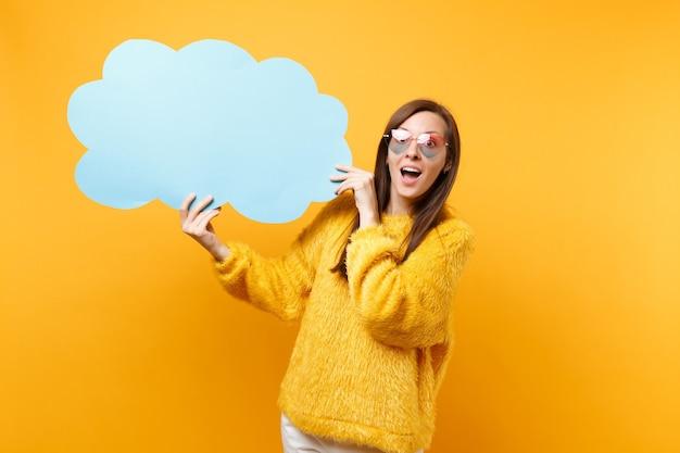 Mulher jovem chocada animada em óculos de coração segurando vazio azul em branco say nuvem, balão de fala isolado em fundo amarelo brilhante. emoções sinceras de pessoas, conceito de estilo de vida. área de publicidade.
