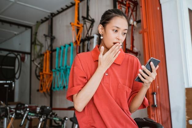 Mulher jovem chocada com as mãos cobrindo a boca ao olhar para a tela do smartphone