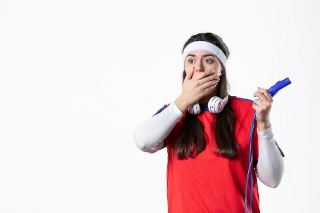 Mulher jovem chocada com vista frontal com roupas esportivas e cordas para pular