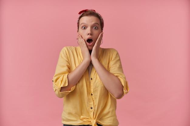 Mulher jovem chocada e assustada em uma camisa amarela com bandana na cabeça e boca aberta mantém as mãos nas bochechas e gritando por cima da parede rosa