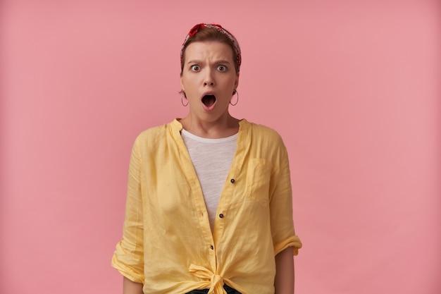 Mulher jovem chocada e atordoada em uma camisa amarela com bandana na cabeça e boca aberta parece espantada e gritando por cima da parede rosa