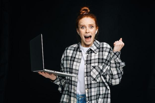 Mulher jovem chocada feliz com a boca aberta segurando um laptop e olhando para a câmera