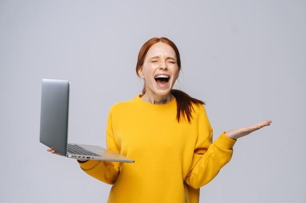 Mulher jovem chocada feliz com os olhos fechados segurando um laptop