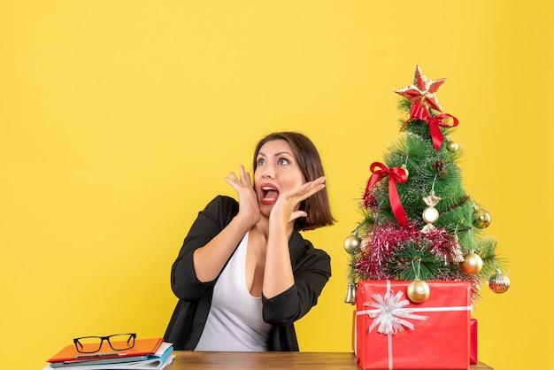 Mulher jovem chocada olhando para algo sentado em uma mesa perto da árvore de natal decorada no escritório em amarelo