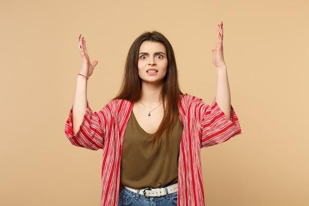 Mulher jovem chocada perplexa em roupas casuais, olhando a câmera, levantando-se espalhando as mãos isoladas em um fundo bege pastel em estúdio. emoções sinceras de pessoas, conceito de estilo de vida. simule o espaço da cópia.
